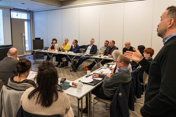 Mange mennesker sitter rundt et møtebord