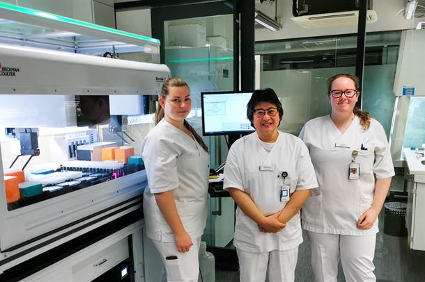 Tre bioingeniører foran en analysemaskin for SARS-Cov-2