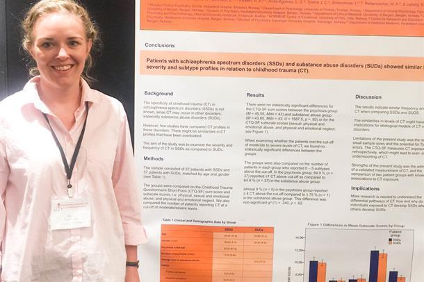 Nina Mørkved foran poster om forskning Barndomstraumer ved psykoselidelser og ruslidelser