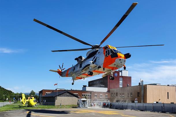 To helikopter med sykehuset i bakgrunnen